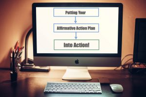 "computer with text ""putting your affirmative action plan into action"""