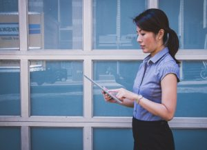 image of an Asian woman working on an ipad. A temporary employee needs to be considered in your affirmative action plan