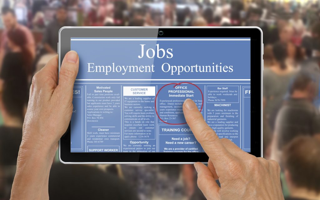 image of a person on tablet looking for a job from an affirmative action employer