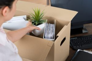 Young Businesswoman Packing Belongings In Cardboard Box At Desk
