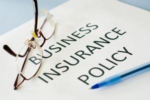 Picture of insurance policy on desk with glasses and pen