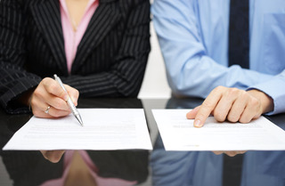 Business employees inspecting contract