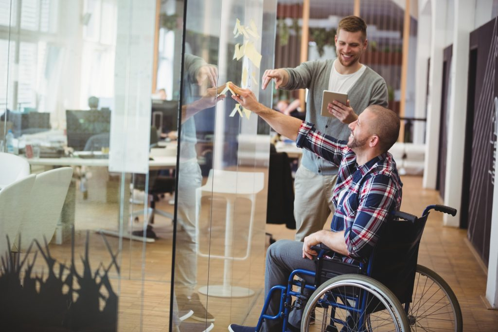 Individual in Wheel Chair Colaborating with other employee